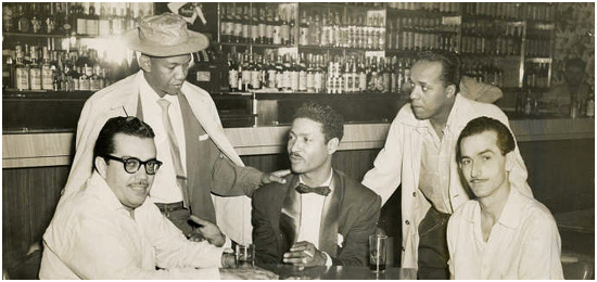 Seated in the middle, Cuban singer and bandleader, Benny Moré. 1953.