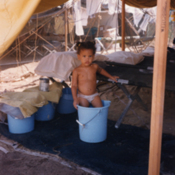 Cuban child standing in a bucket at Guantanamo Bay Naval Base, 1990s