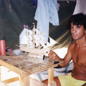 Cuban refugee in a Guantanamo Bay camp making a model sailboat, 1990s