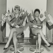 Two Pan Am stewardesses hold flags from countries serviced by Pan American World Airways