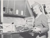 A Pan Am stewardess prepares trays of food in the galley of a Boeing 707